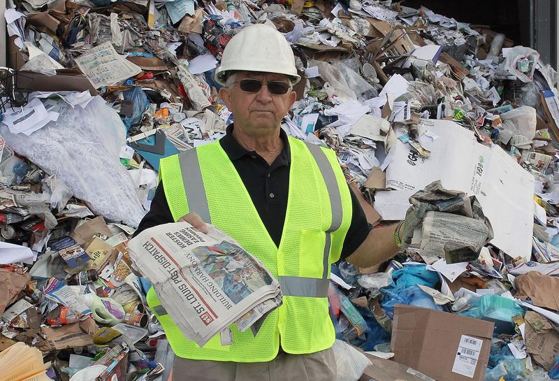 Resource Management sales manager Gary Gilliam holds up pieces of wet (right) and dry newspaper. Wet paper won't make it through the single-stream process and will end up at a landfill.