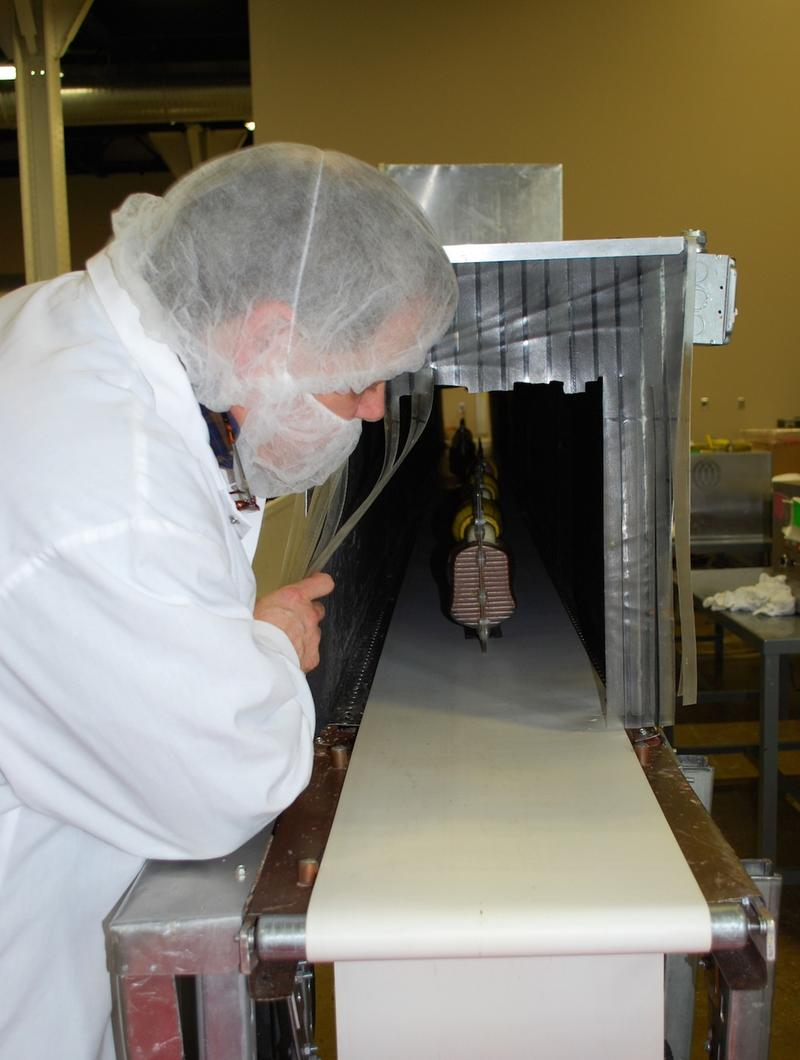 The cooling tunnel completes the solidification process. Dave Owens, Bissinger's chocolatier, checks on a mold.