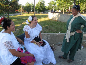 Cecilia Nadal (standing at right in green) talks with Yanith Carranza (left) and Elizabeth Morales in Amherst Park after the unity concert. Morales came from the Festival of Nations in Tower Grove Park.