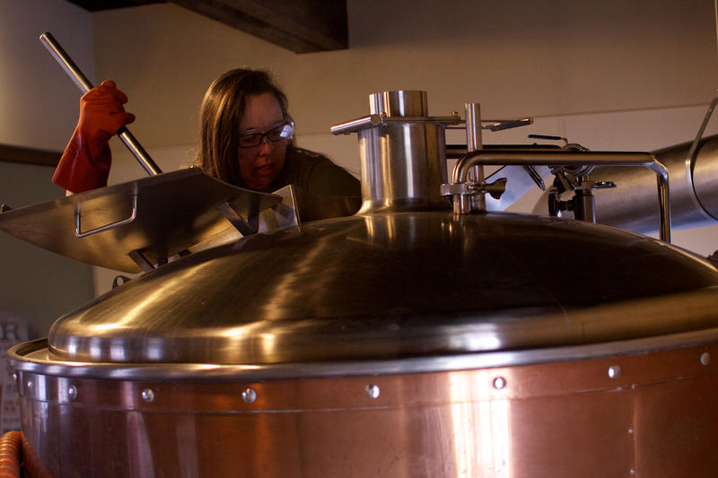 Cheryl Fields ensures the boiling grain is stirred as it's added