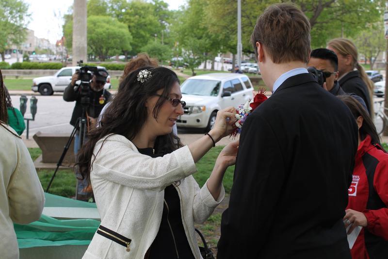 Alderwoman Megan Green, D-15th Ward, pins a boutonniere on Ben Murray before Tuesday's Board of Aldermen meeting.