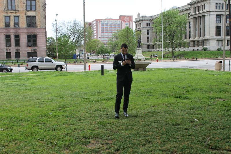 Patrick Brown, a staffer for St. Louis Mayor Francis Slay, checks his phone near Poelker Park.