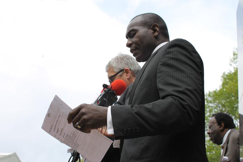 Board of Aldermen President Lewis Reed flips through the agenda during a Board of Aldermen meeting that took place outdoors.