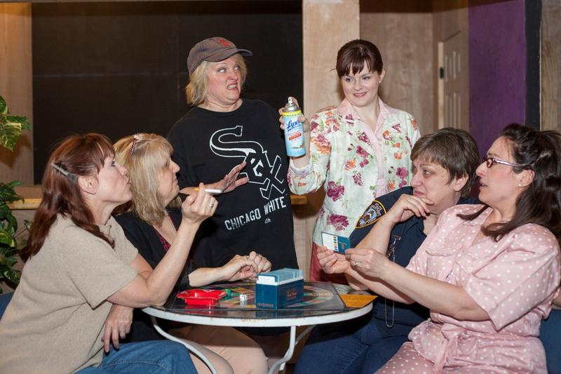 Olive, played by Kim Furlow, and Florence, played by Colleen Backer, both standing, surrounded by friends, in in Dramatic License's