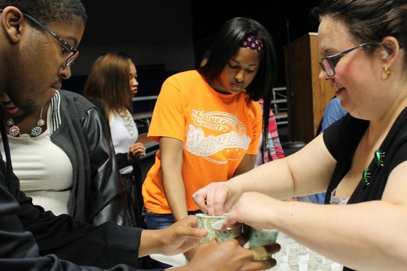 Students handing off teacups to art teacher Michelle Motil