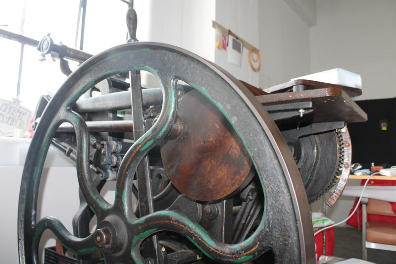 Lauren Cardenas, owner of PIECRUST, prints on this antique letterpress. You can hear from her in the audio version.