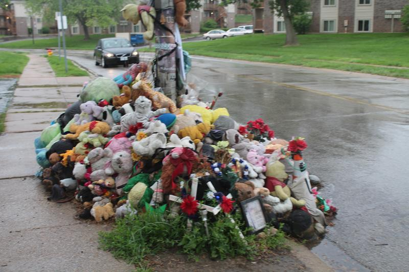 A pile of stuffed animals are situated near the street.