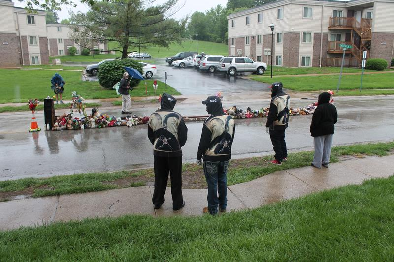 Michael Brown, Sr., (second from the right) stands in front of the temporary memorial dedicated to his son Michael Brown, Jr. The elder Brown helped dismantle the memorial on Wednesday.
