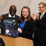 Incoming Westminster College President Benjamin Akande accepts a school T-shirt from Molly Dwyer, president of the school's student government association, as retiring president George Forsythe looks on.