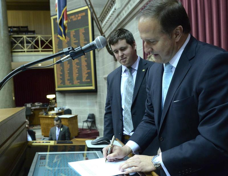 Rep. Scott Fitzpatrick watches as House Speaker John Diehl signs the veto override of HB 150. unemployment