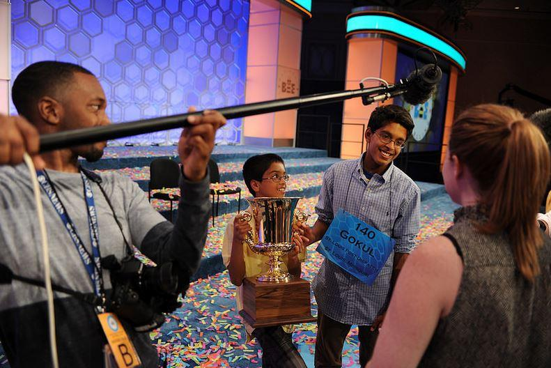 Gokul Venkatachalam talks with media as his younger brother holds the National Spelling Bee trophy