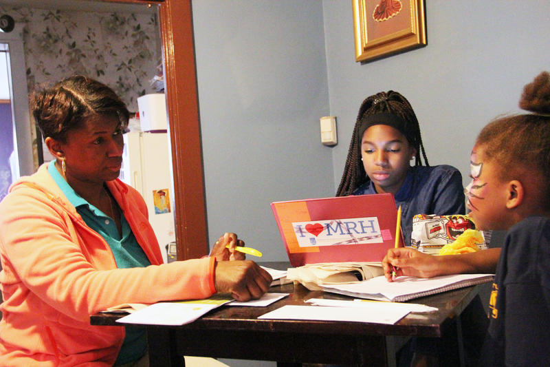 From left, SheRon Chaney helps her daughters Anandra and BrenNae with homework at their dining room table.