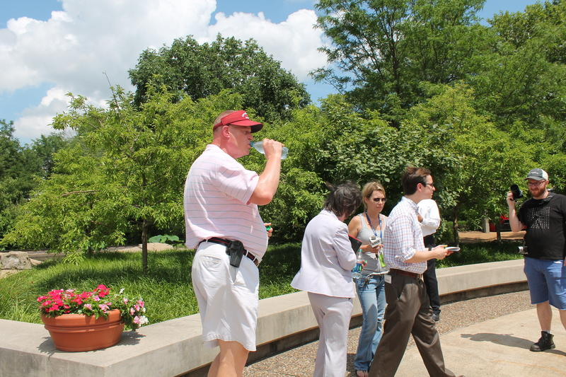 Jeffry Smith drinks a bottle of water inside the Saint Louis Zoo while wearing an empty gun holster on Saturday, June 13, 2015.