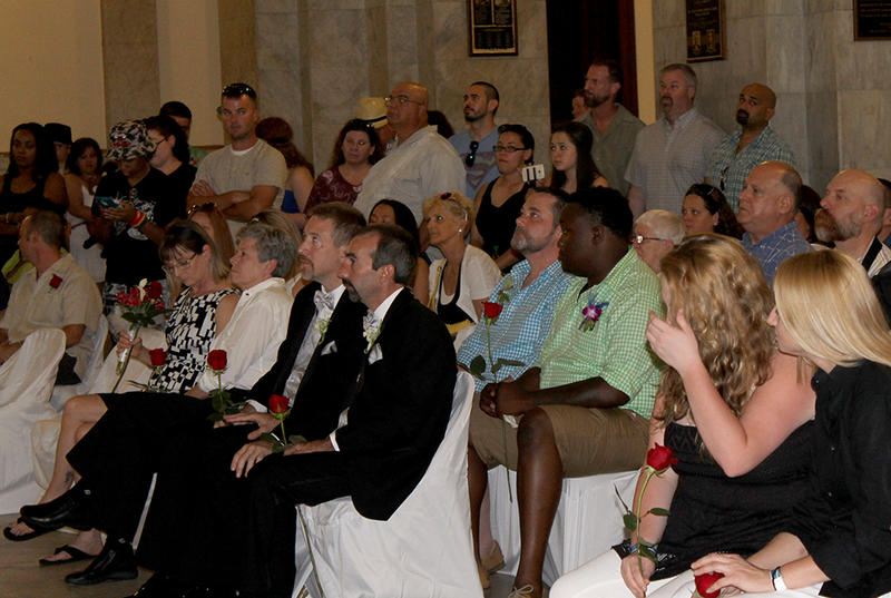 Same-sex couples and their guests watch a commitment ceremony before their wedding ceremony on Saturday, June 27, 2015 in St. Louis.
