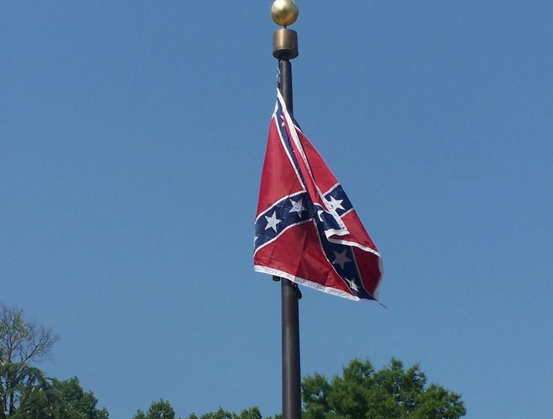Confederate battle flag beside the Confederate Monument in front of the South Carolina Statehouse