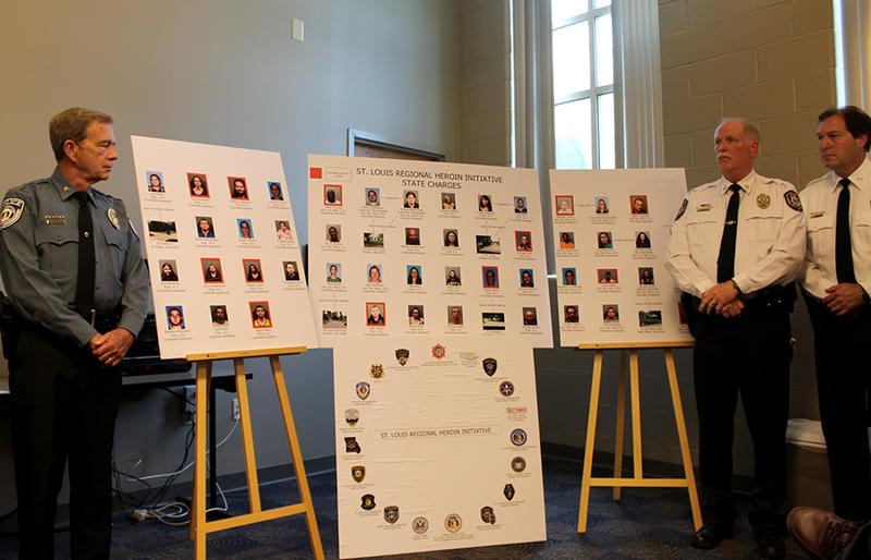 Members of the St. Louis Regional Heroin Initiative flank posters listing those arrested for heroin-related charges Wednesday, June 10, 2015 in the St. Charles City Police Department.
