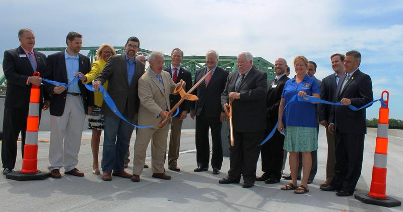 State and local officials pose for a ceremonial ribbon cutting to mark the completion of I-64's eastbound Daniel Boone Missouri River Bridge.