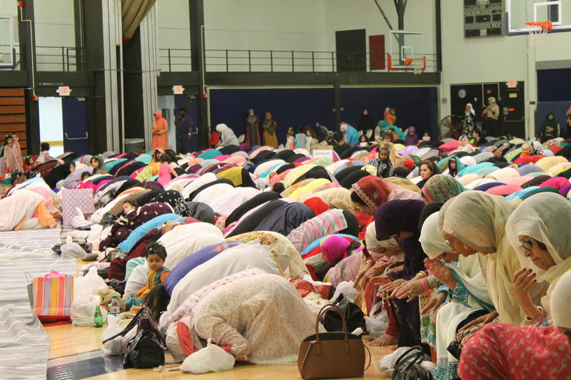 Women bow on prayer rugs pointed in the direction of Mecca during an Eid prayer service in St. Louis.