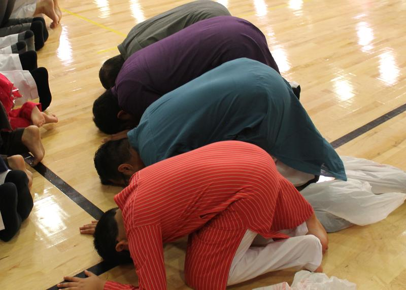 Men bow in prayer in the direction of Mecca during an Eid service put on by the Islamic Foundation of Greater St. Louis.