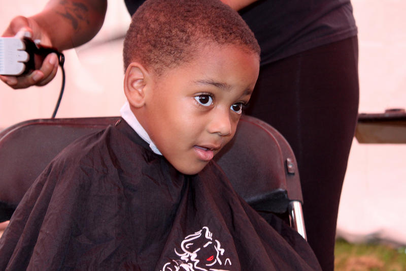 Chase Bond, 4, of Ferguson gets a haircut from Deyana Williams of the Elaine Steven Beauty College Saturday, July 25, 2015 in Forestwood Park during the Day of Hope outreach fair.