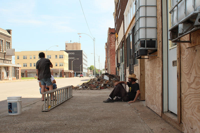 Galen Gondolfi sits outside one of the rennovated storefronts that will become studio and exhibition space