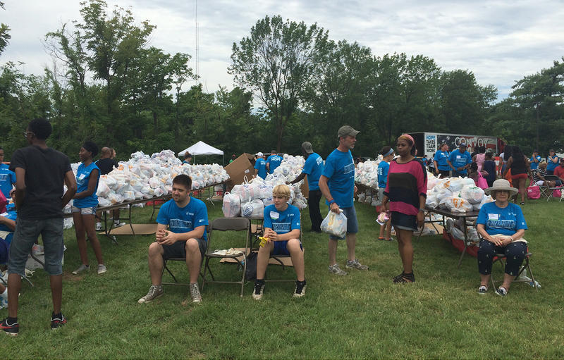 Tables filled with bags of groceries line the exit of the community outreach fair in Forestwood Park in Ferguson Saturday, July 25, 2015. Convoy of Hope and its local partners gathered 35,000 pounds of groceries to give away.