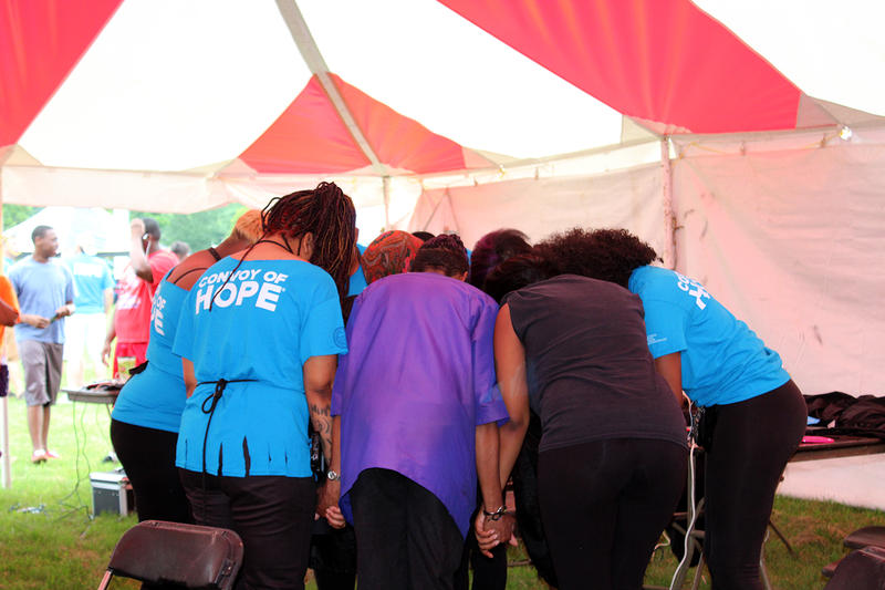 Hair stylists from Elaine Steven Beauty College pray in a circle before starting the free haircuts offered at the Convoy of Hope outreach Fair in Ferguson Saturday, July 25, 2015.