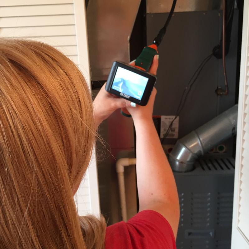 An asthma field inspector checks a heating and air conditioning system during a home assessment.