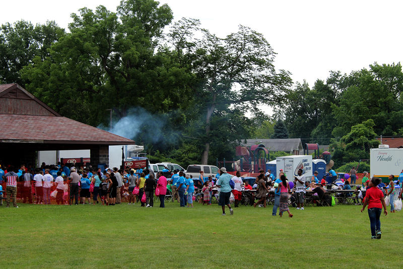 Smoke rises on the outdoor grills in Forestwood Park Saturday July 25, 2015 in Ferguson as people line up for a free hotdog lunch.