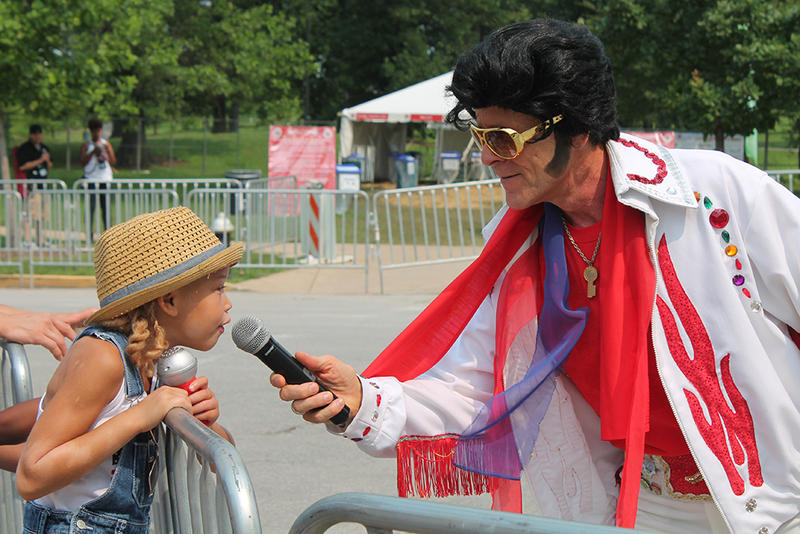 Olivia Meysmith,  6, leans over the parade rail to sing with an Elvis impersonator on Saturday, July 4, 2015.