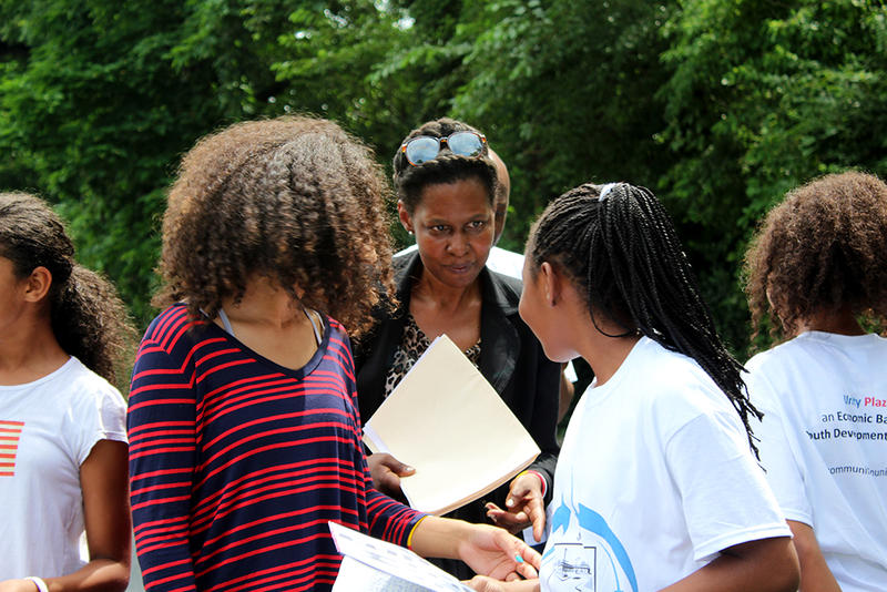 Theresa Bradley passes out poems for a reading Saturday, July 11, 2015. Bradley started a poetry club to keep teens busy this summer. Three of the girls are her nieces, and they  say they aren't officially part of the poetry club.
