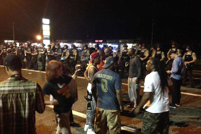 Protesters and police after shooting on the one year anniversary of Michael Brown's death