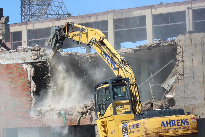 An excavator with an eight-foot-long claw takes down chunks of the Wilco Building at the Carter Carburetor site on Monday.