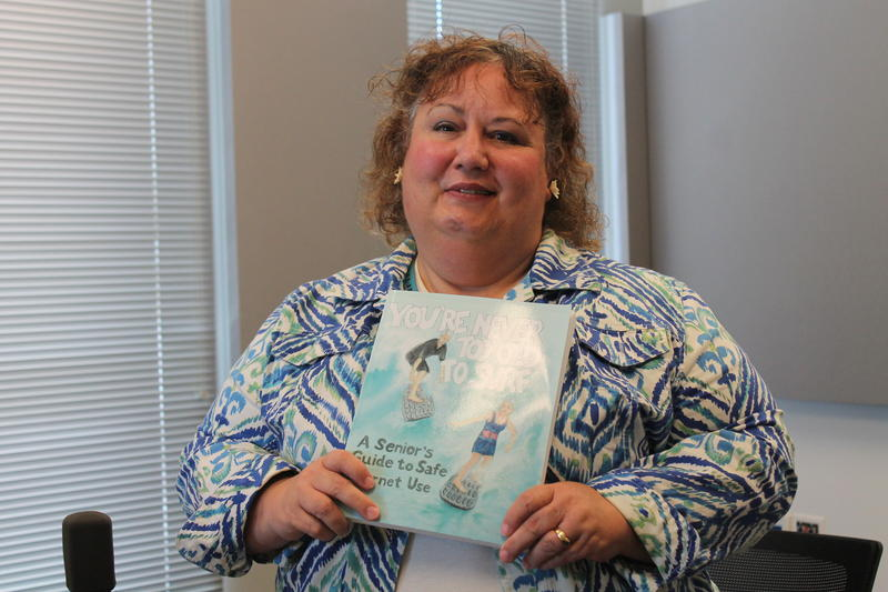 "Vicki Sauter holds her book, ""You're Never Too Old to Surf."""