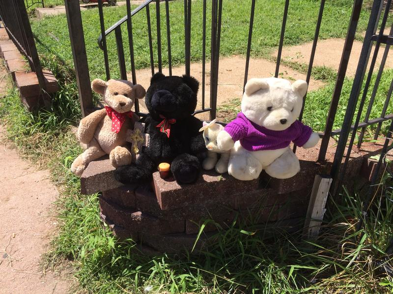 Teddy bears line the fence of the flat where Mansur Ball-Bey was killed earlier this week.