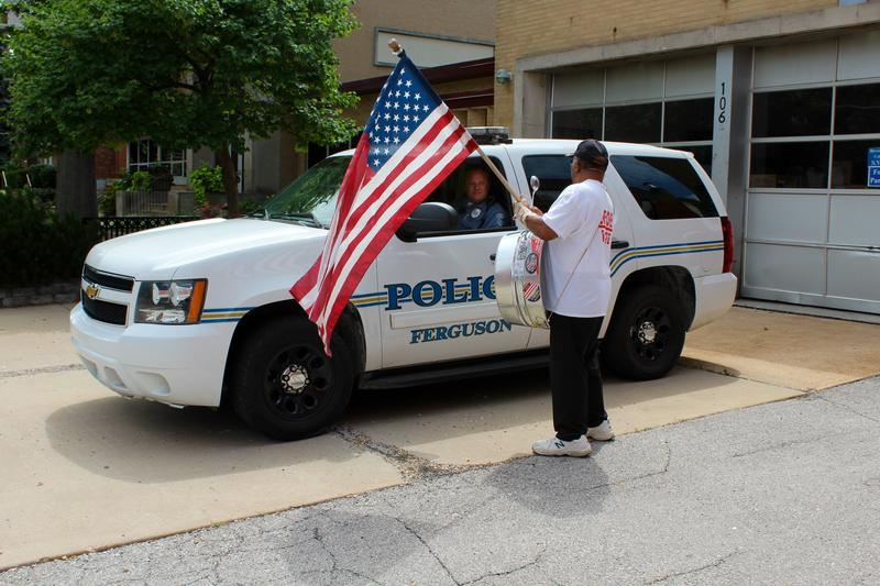 A man with an American flag stands in front of a Ferguson Police car earlier in July.