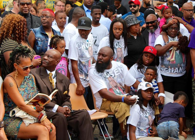 Michael Brown, Sr., sits in a chair near his family to commemorate his son's death.