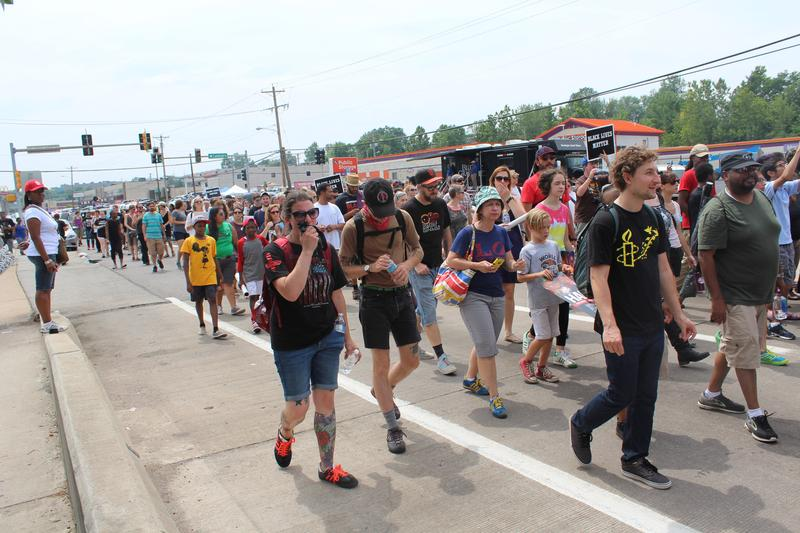 Hundreds of people marched down West Florissant Avenue to mark Brown's death.