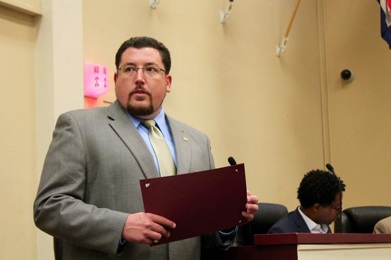 Ferguson Mayor James Knowles III prepares to hand a resolution to a city resident. Knowles reflected on how his city's changed since Michael Brown's death earlier this week.