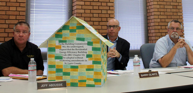 The St. Louis County Building Commission (Jeff Aboussie, Barry Glantz and John Finder, right) listens to Sierra Club supporters on Wednesday. The model house is covered with the names of 529 area residents who want stricter energy efficiency standards.