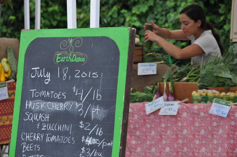 A vendor sells vegetables from Ferguson's EarthDance Farms at a weekly farmer's market.
