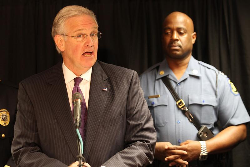 Gov. Jay Nixon announces that he has asked the state commission overseeing police officer training to update standards around tactical training, cultural competency, and officer wellness on August 6, 2015. Behind him is Mo. State Highway Patrol Capt. Ron
