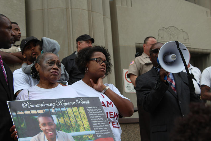 The grandmother of Kajieme Powell holds a sign on the steps of the Carnahan Courthouse as a speaker shouts in a bullhorn Wed. Aug. 19, 2015. Powell died one year ago Wed.