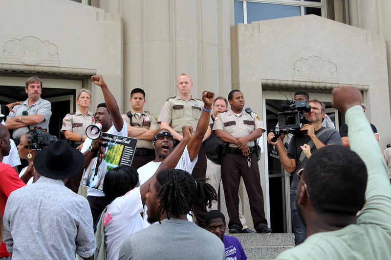 Protesters chant as police guard entrance to the Carnahan Courthouse on Wed. Aug. 19, 2015  one year after two St. Louis police officers shot and killed Kajieme Powell.