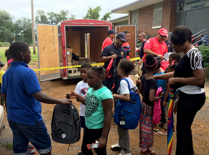 Members of the Local 23 firefighters union pass out school supplies to parents and children Saturday, August 22, 2015 in East St. Louis' Lincol Park.