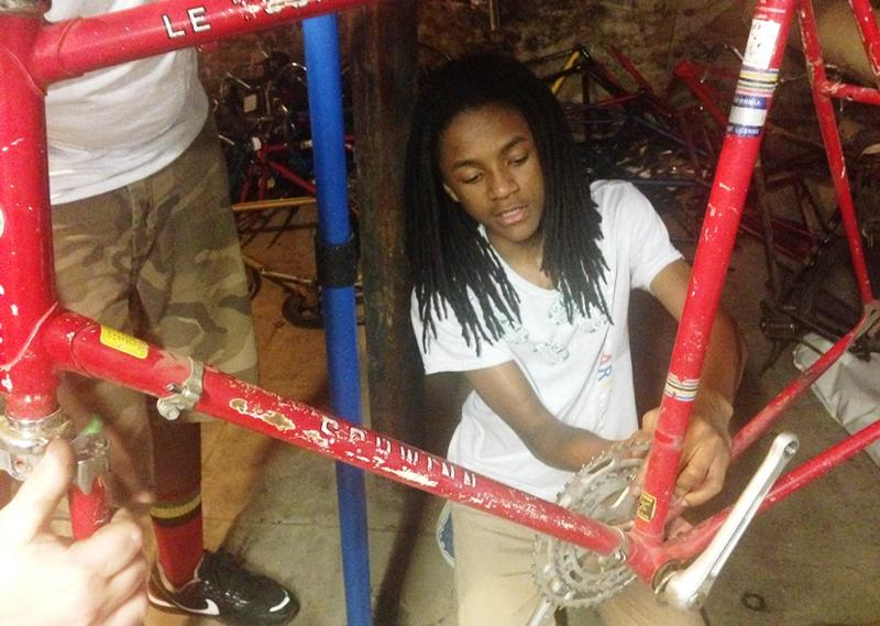 ArtWorks apprentice Tyson Johnson taking apart a bike to later make coat racks and coat hangers