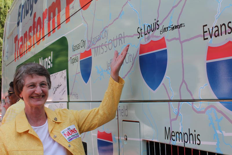 Sister Judith Best of St. Louis gestures to the side of the bus she'll be riding in on a seven-state social justice tour with NETWORK's