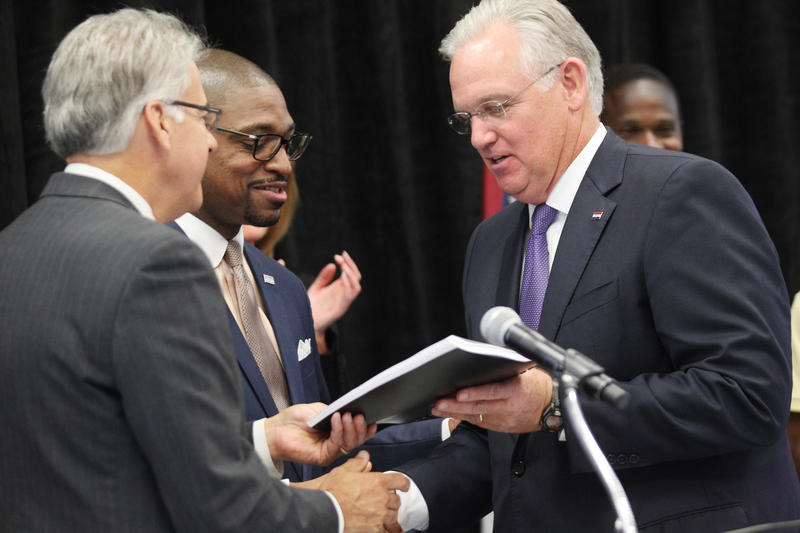 Missouri Gov. Jay Nixon accepts a copy of the Ferguson Commission's recomendations from co-chairs Rich McClure (L) and Rev. Starsky Wilson during a press conference in Florissant.