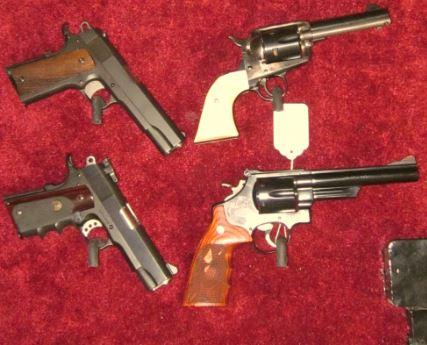 Four hand guns on a red cloth.