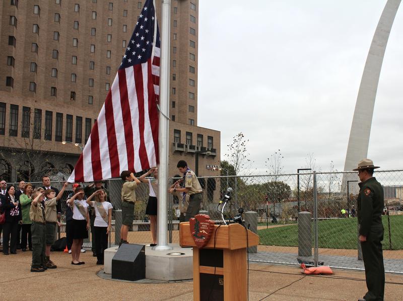 Children raise the flag before the anniversary ceremony.